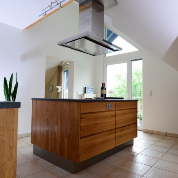 Holzküche in Eiche mit Granit-Arbeitsplatte, Backofen und Dampfgarer eingebaut in einer Nische