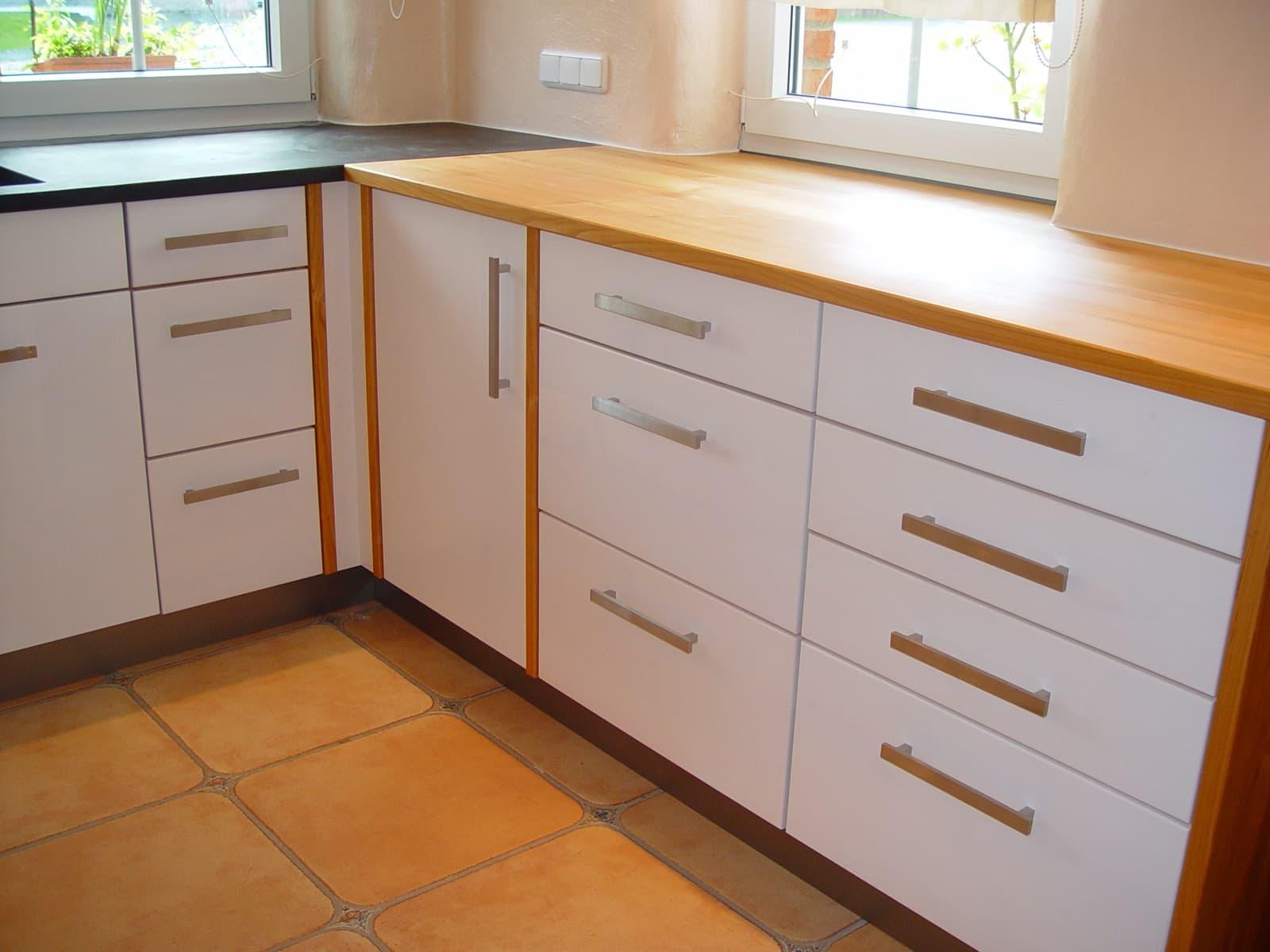 Massivholzküche mit Fronten weiß gebeizt und Arbeitsplatten in Granit / Kirschbaum massiv