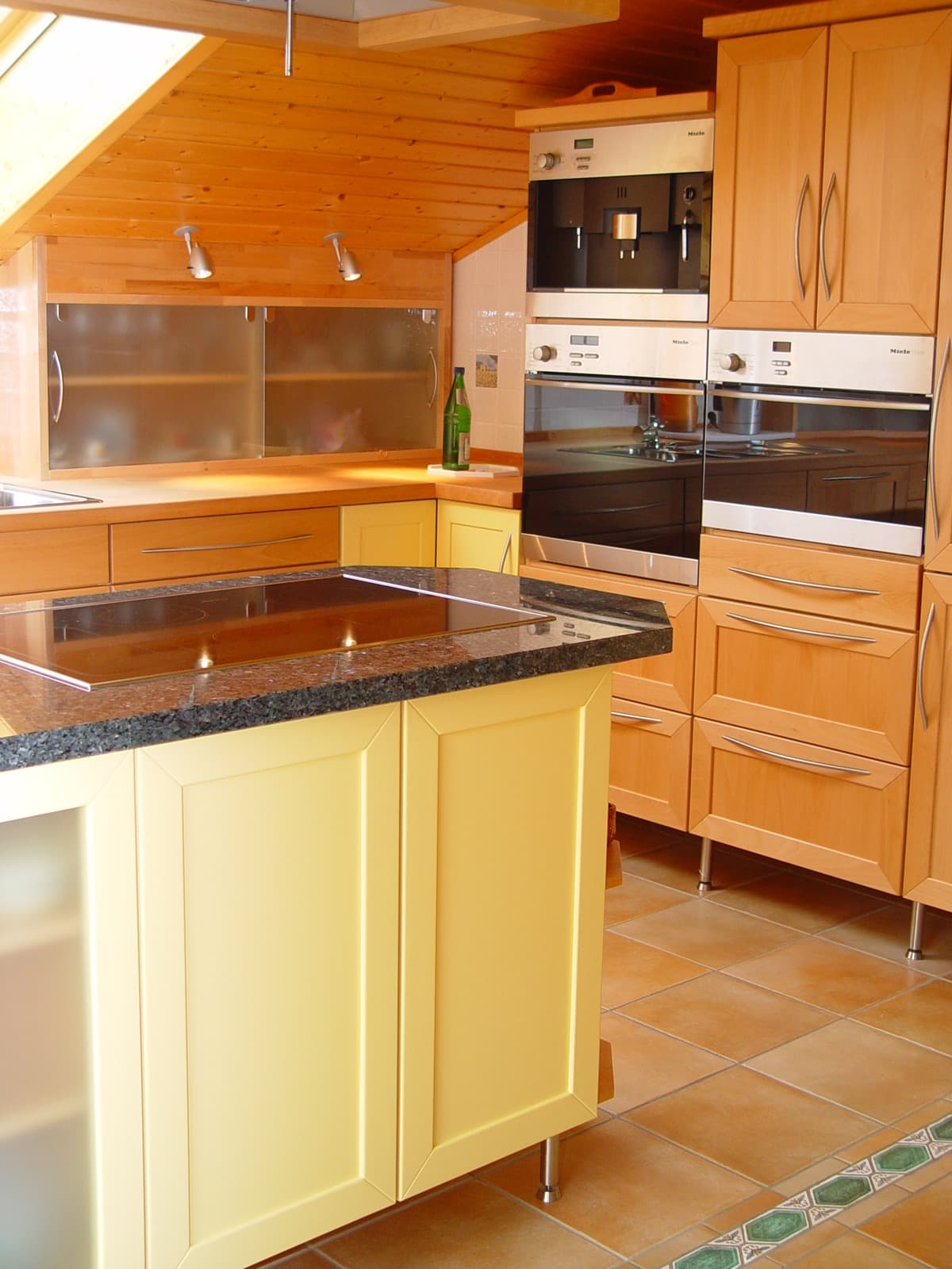 Massivholzküche in der Dachschräge mit Glas-Schiebetüren und deckend lackierten Fronten
