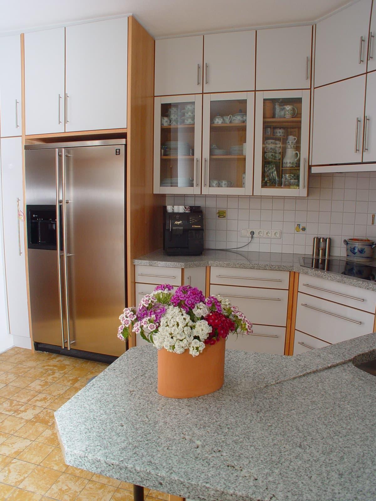 Raumhohe Küche mit Akzenten in Buche und Granit-Arbeitsplatte