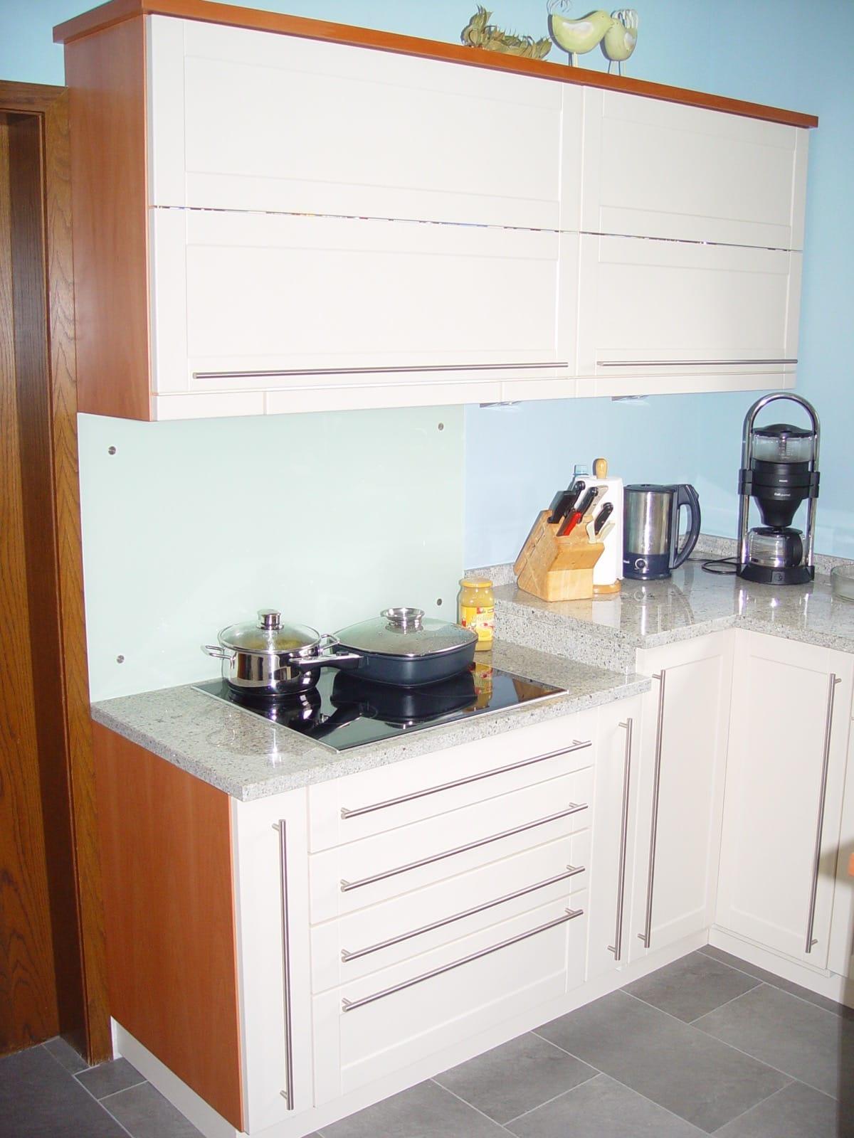 auffallende Küche mit Folienfronten und abgesetzter Kochzeile und Granit-Arbeitsplatte
