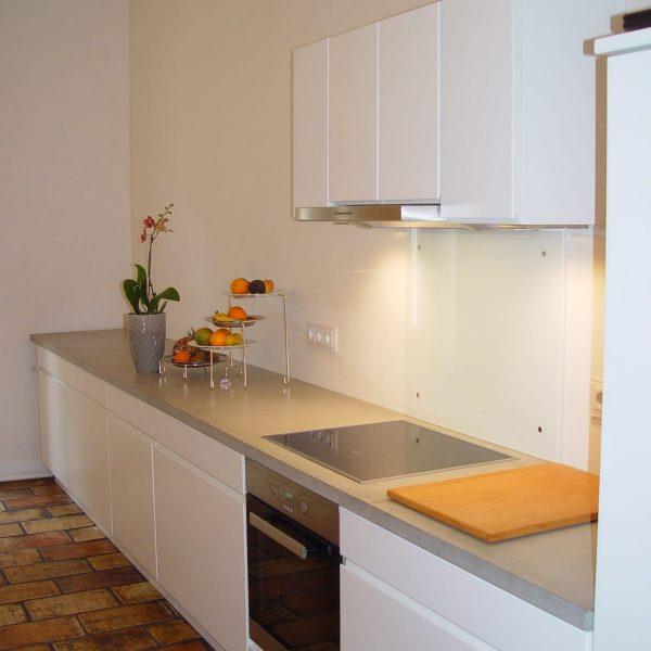 auffallender Küchenblock in deckend weiß matt lackiert und Beton-Arbeitsplatte
