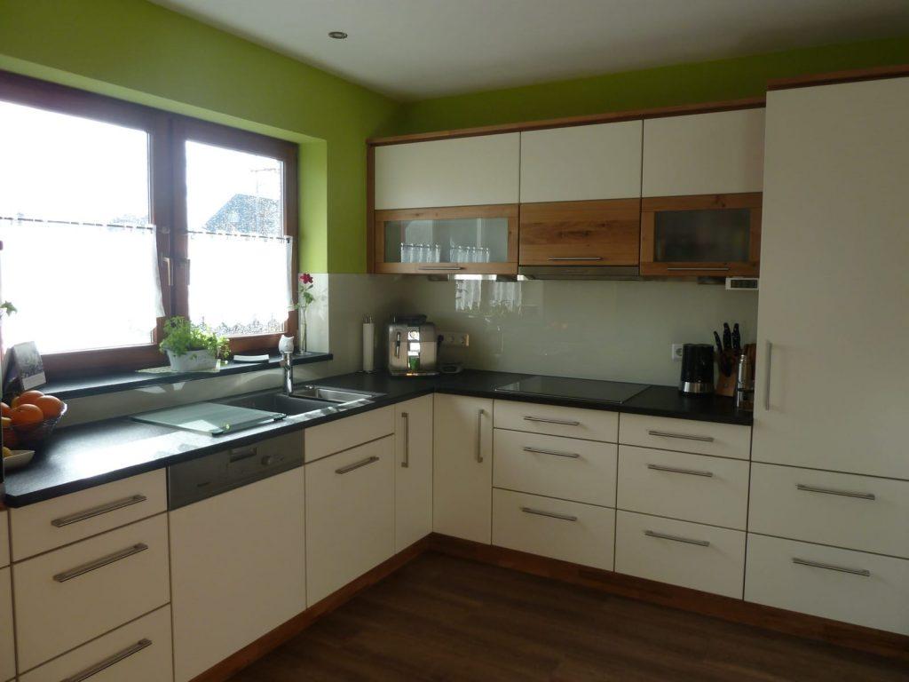 zeitlose Küchenzeile in deckend weiß matt lackiert mit Akzenten in Eiche Wildholz