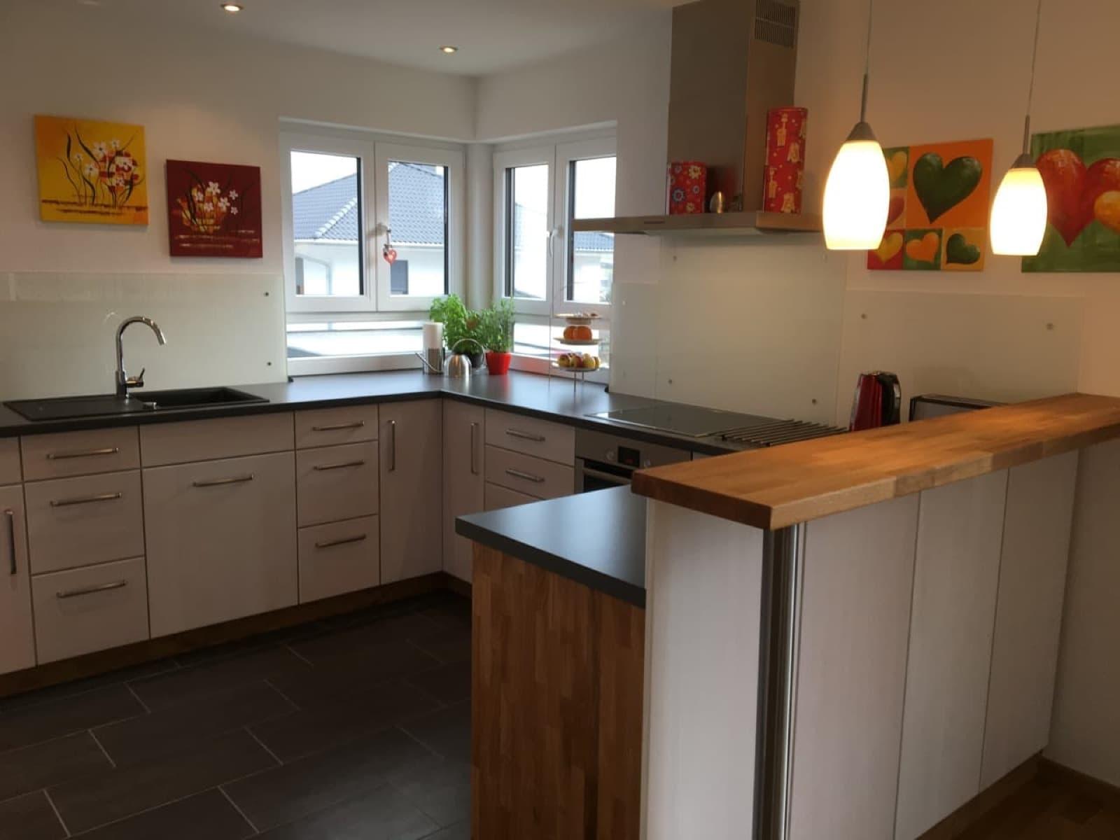 Moderne weiß lasierte Fronten in Kombination mit Eiche Wildholz geben diese Küche einen besonderen Flair