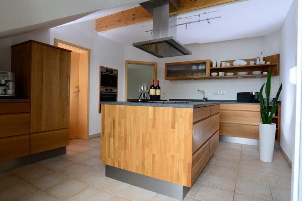 zeitlose Holzküche mit Insellösung sowie Granit-Arbeitsplatte, Backofen und Dampfgarer in die Wand eingebaut