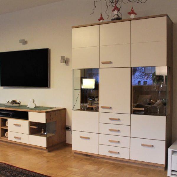Wohnzimmerschrank in cremeweißer Front und Holzakzente in Eiche massiv